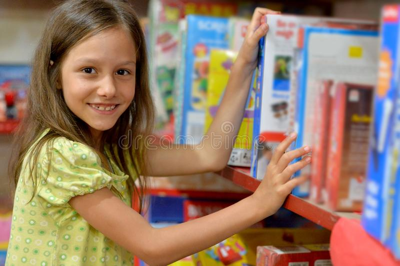 Portrait of cute little girl choosing book in bookstore. Portrait of little girl choosing book in bookstore royalty free stock image