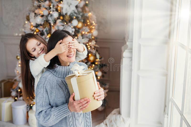 Portrait of little girl closes mother`s eyes, congratulates her with New Year or Christmas, stand near window in living room, have stock photography