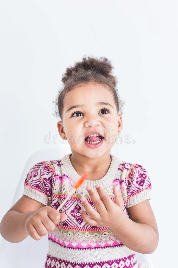 Portrait of a little girl in a colorful dress with a lollipop on a white background royalty free stock photos