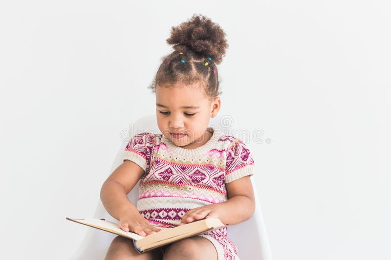 Portrait of a little girl in a colorful dress reading a book on a white background.  royalty free stock photo