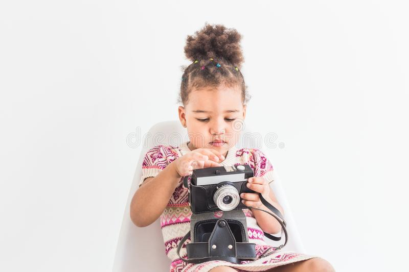 Portrait of a little girl in a colorful dress taking pictures on an old vintage camera stock photo