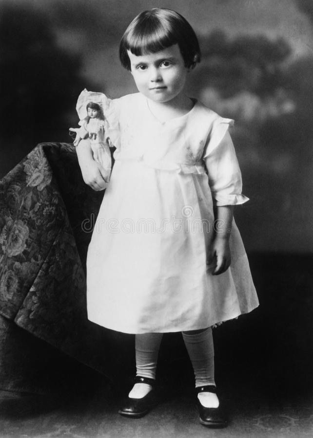 Portrait of little girl with doll. (All persons depicted are no longer living and no estate exists. Supplier grants that there will be no model release issues stock images