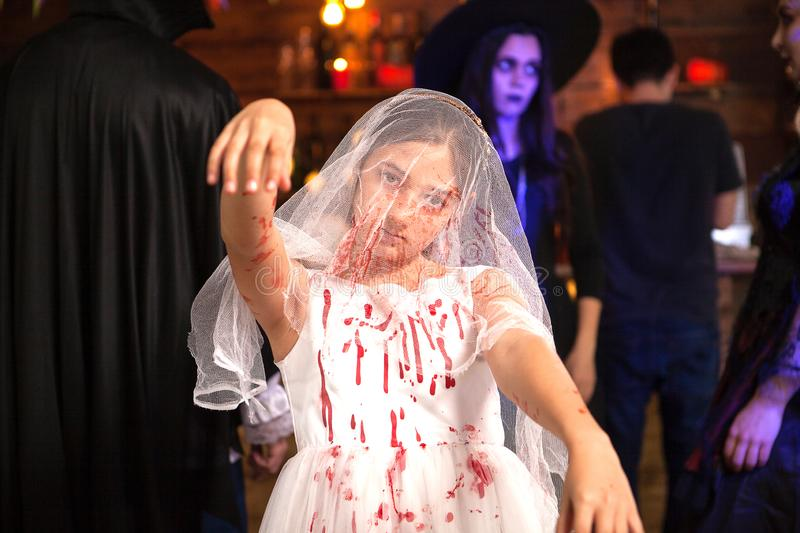 Portrait of little girl dressed up like a bride covered with blood at halloween party stock photo