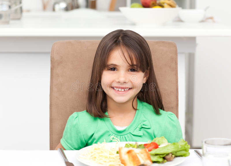 Portrait of a little girl eating pasta and salad. In the kitchen stock photography