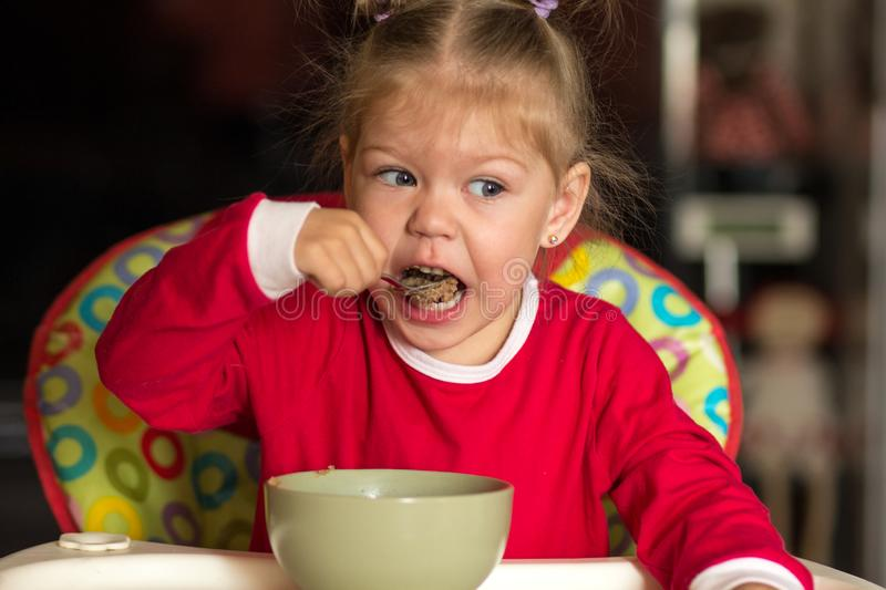 Portrait of little girl eating porridge using spoon sitting in feeding chair royalty free stock images