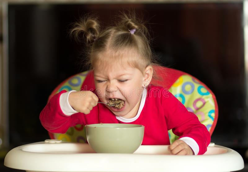 Portrait of little girl eating porridge using spoon sitting in feeding chair royalty free stock photo