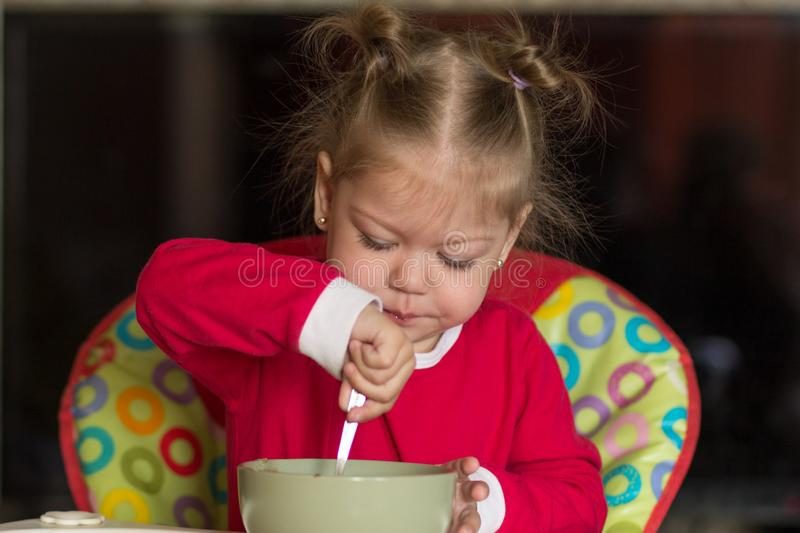 Portrait of little girl eating porridge using spoon sitting in feeding chair royalty free stock image