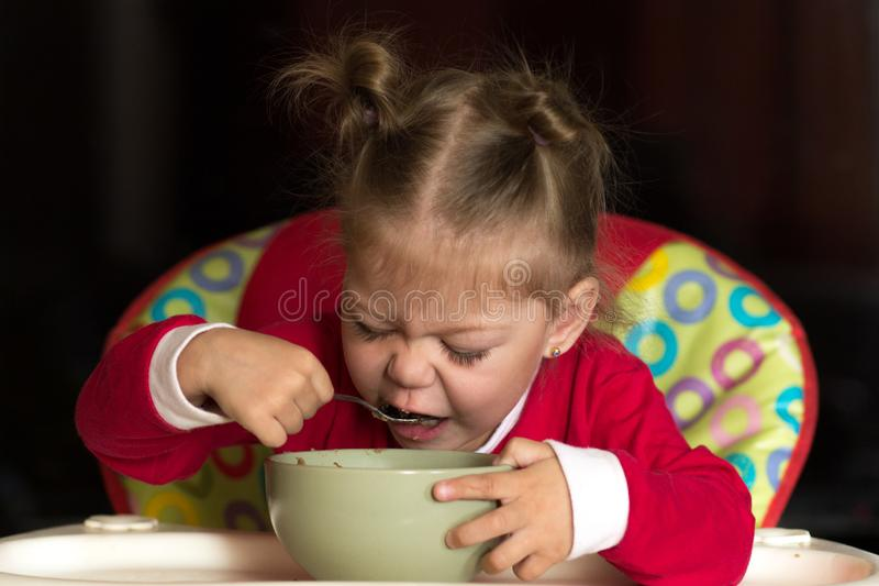 Portrait of little girl eating porridge using spoon sitting in feeding chair stock images