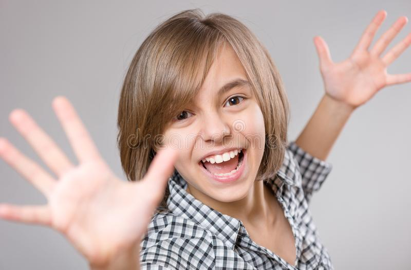 Portrait of little girl. Emotional portrait of little girl celebrating, gesturing, keeping arms raised and expressing positivity. Funny teenager, on gray royalty free stock photography