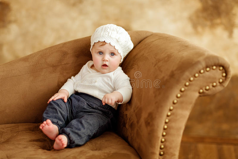 Portrait of a little girl eyed little girl in a white beret sitting on the couch on a brown background in studio stock photo