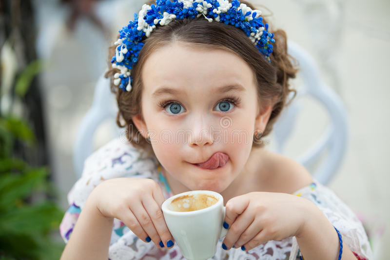 Portrait of little girl in a floral dress drinking coffee royalty free stock images