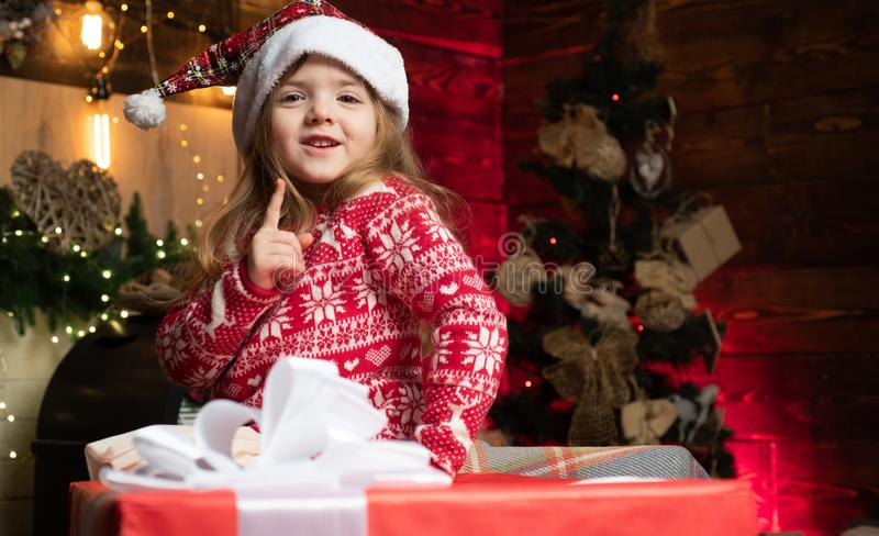 Portrait little girl with gift on wooden Christmas background. Cute little girl coming to Christmas tree and looks at royalty free stock images