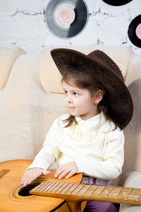 Portrait of the little girl with a guitar in hands. Portrait of the little girl in a leather hat and with a guitar in hands royalty free stock photography