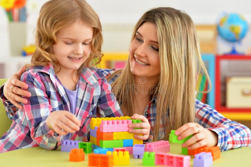 Portrait of little girl and her mother playing colorful plastic blocks together in her room. Cute little girl and her mother playing colorful plastic blocks stock photography