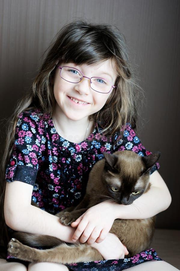 Portrait of little girl holding burmese cat. Portrait of toddler girl posing with burmese cat royalty free stock images