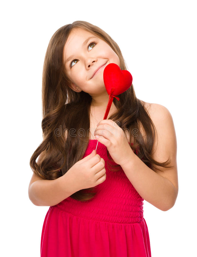 Portrait of a little girl. Holding red heart and daydreaming, isolated over white royalty free stock image