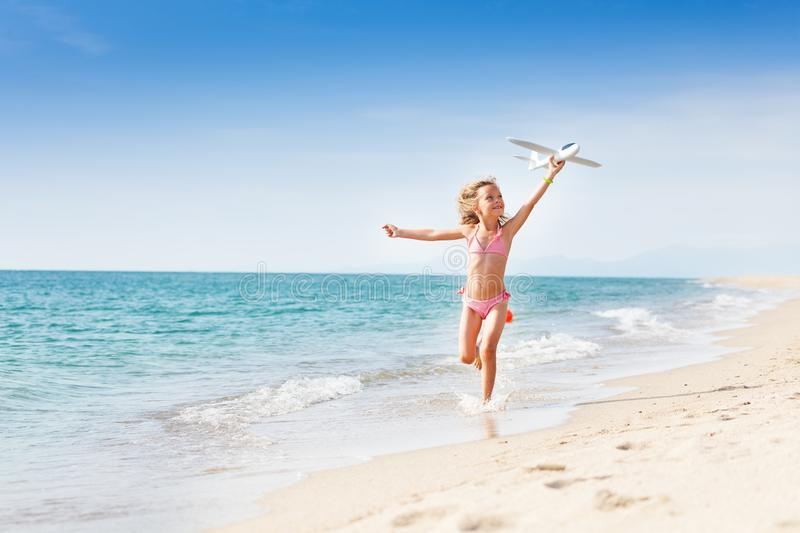 Little girl running on the coast with toy plane stock images