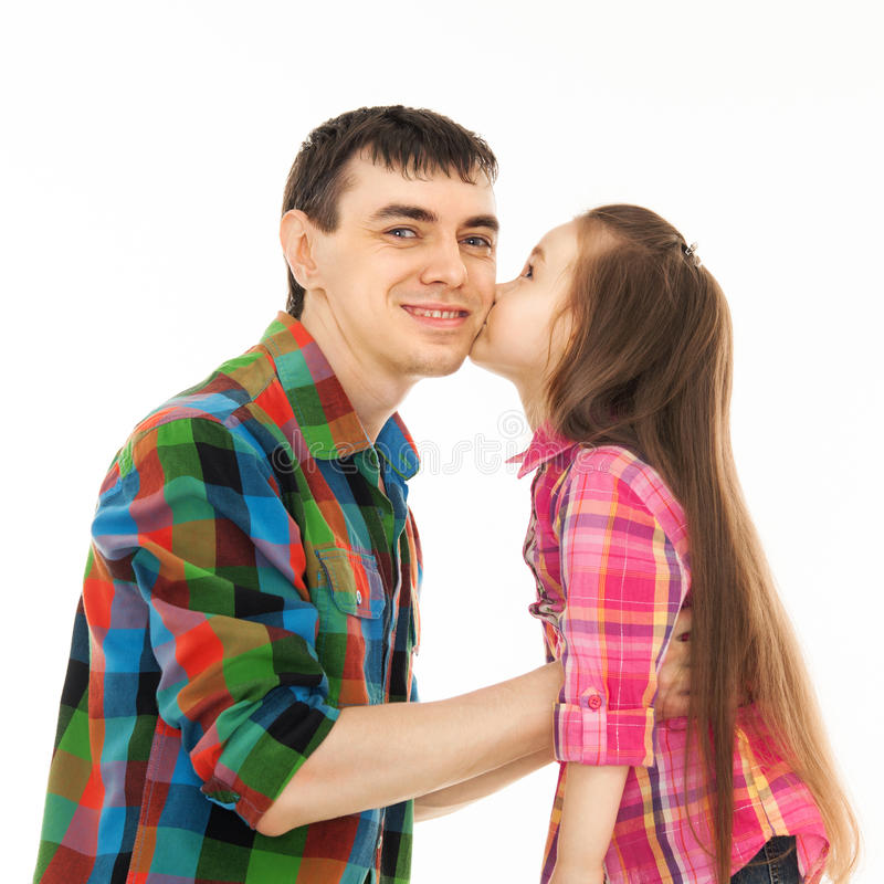 Portrait of little girl kissing her father stock photos