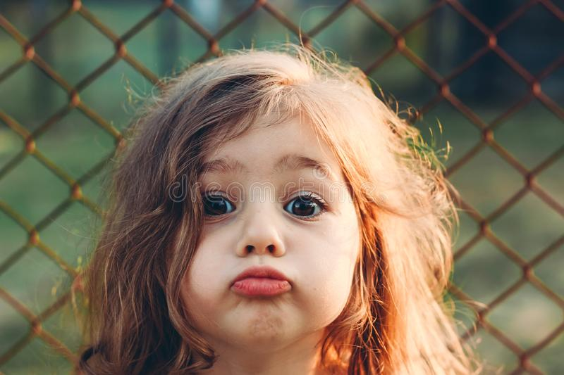 Portrait of cute little Girl with kissing lips looking at camera royalty free stock photo