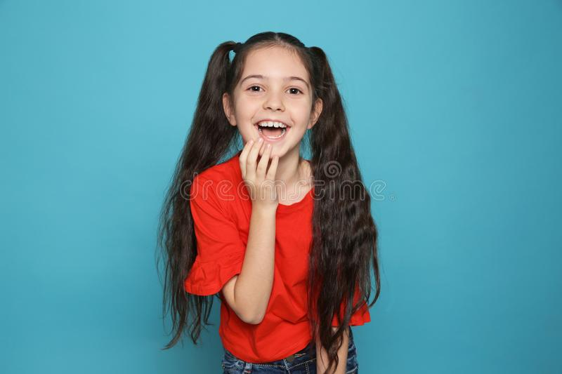 Portrait of little girl laughing. On color background stock photos