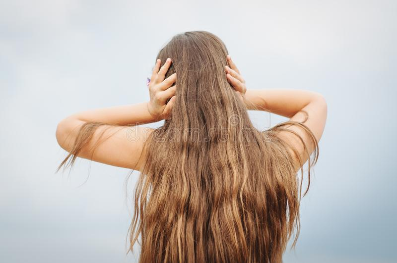 Portrait of a little girl with long hair, back, covers her ears with her hands. Portrait of a little girl with long hair, rear view from the back, covers her stock photo