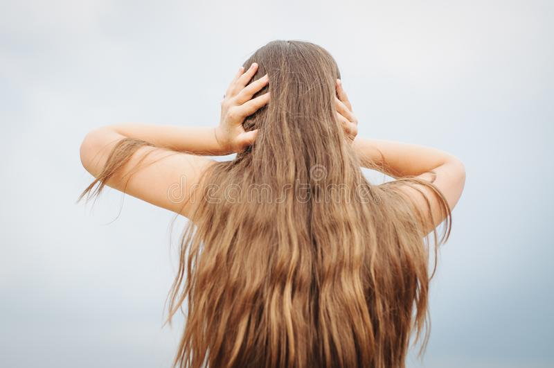 Portrait of a little girl with long hair, back, covers her ears with her hands. Portrait of a little girl with long hair, rear view from the back, covers her stock image