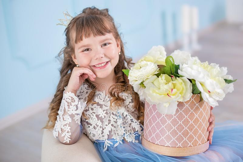 Portrait of little girl in luxurious dress posing in decorated blue studio with bouquet of flowers on retro sofa divan.  stock image