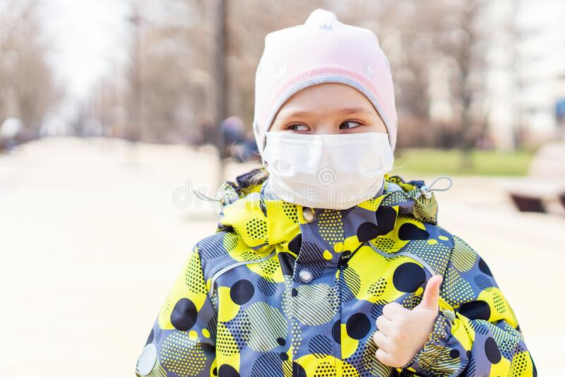 Portrait of a little girl in a medical protective mask on her face, Covid-19 coronavirus pandemic, virus protection.  stock image