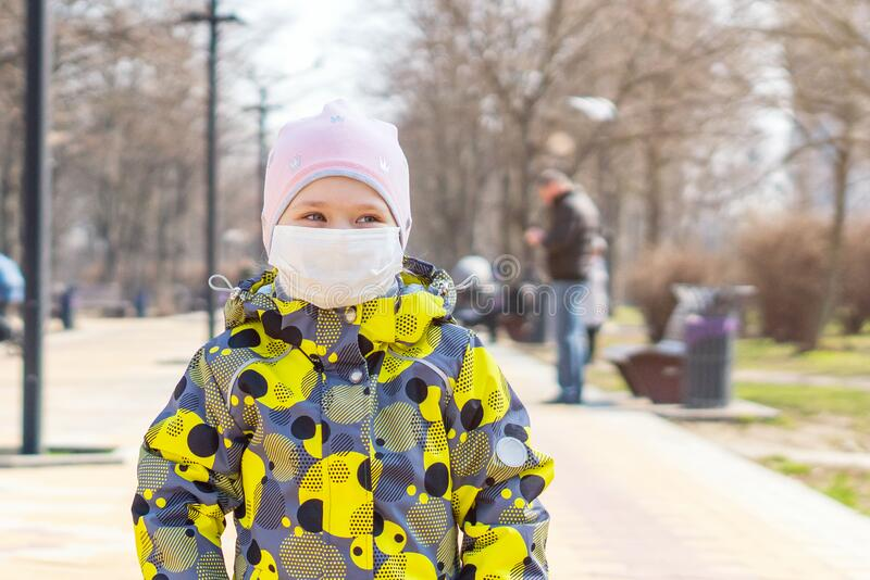 Portrait of a little girl in a medical protective mask on her face, Covid-19 coronavirus pandemic, virus protection.  royalty free stock photography