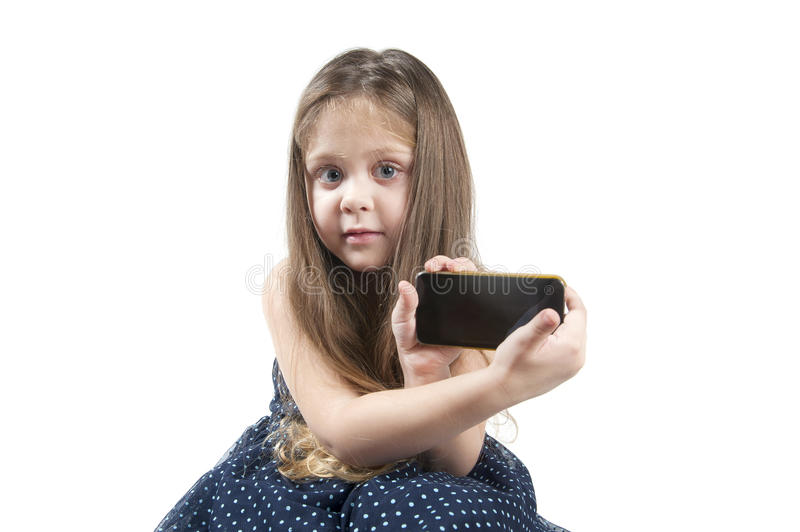 Portrait of a little girl with mobile phone in hand. stock image