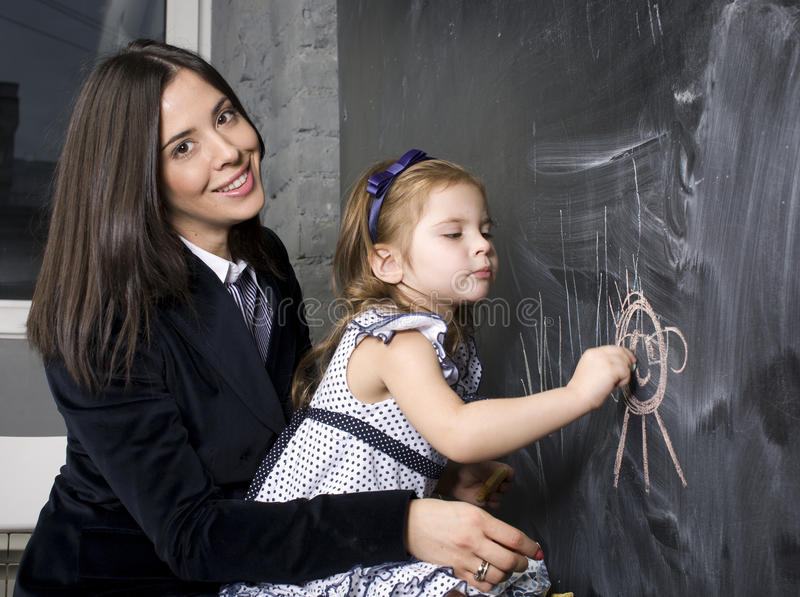 Portrait of little girl with mother at blackboard, making lessons royalty free stock photography