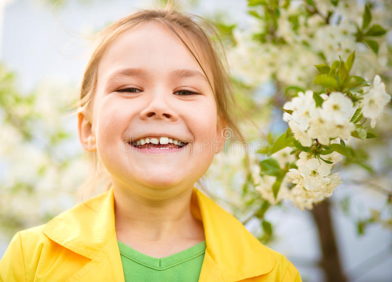 Portrait of a little girl near tree in bloom. Portrait of a cheerful little girl near spring tree in bloom royalty free stock photography