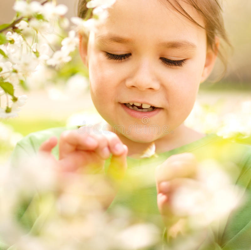 Portrait of a little girl near tree in bloom. Portrait of a cheerful little girl near spring tree in bloom stock photography