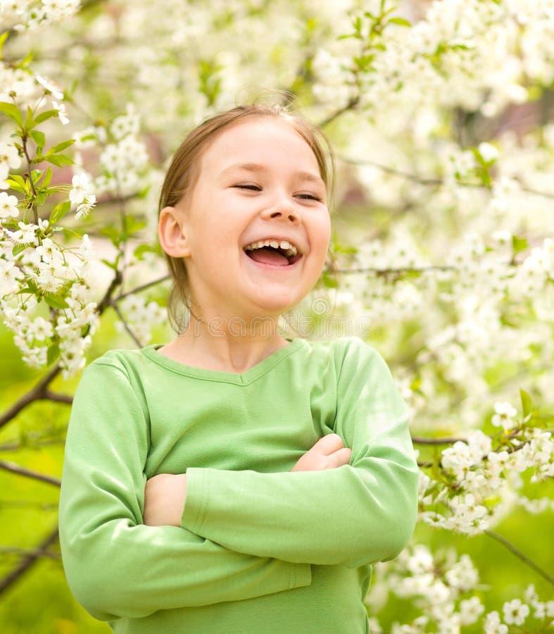 Portrait of a little girl near tree in bloom. Portrait of a cheerful little girl near spring tree in bloom stock photos