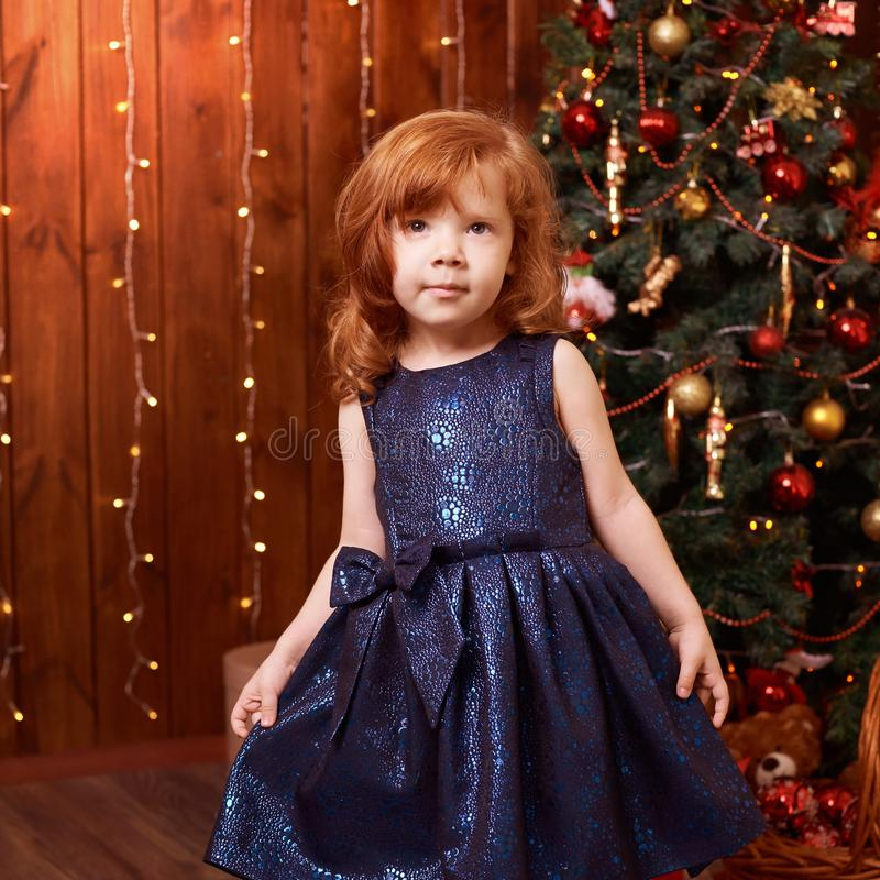 Portrait little girl. New Year xmas child. Christmas eve holiday. interior. Blue dress stock photos
