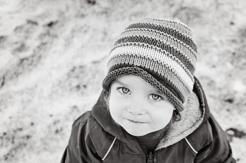 Portrait of little girl one year old looking straight to the camera in winter park. Black and white. stock image