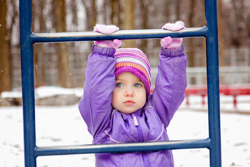 Portrait of little girl one year old playing outside in winter park playground. Toddler girl looking straight to the camera. royalty free stock photos