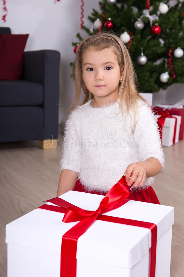 Portrait of little girl opening big gift box near Christmas tree stock photography