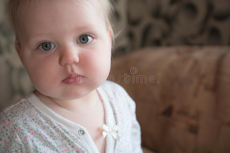 Portrait of a little girl in pajamas sitting on the couch. The little girl just woke up and sits on the couch in light surprise stock image