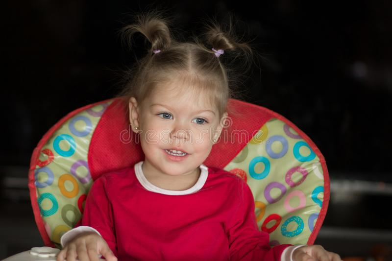 Portrait of little girl with pensive look and smiling sitting in the chair royalty free stock photos
