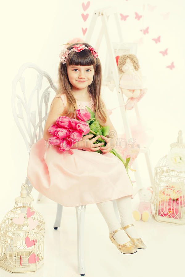 Portrait of a little girl, pink tulips in hands royalty free stock image