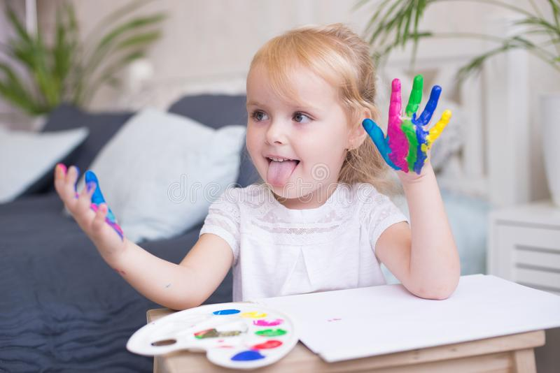 Portrait of little girl playing with paints. Blonde girl 4-5 years old royalty free stock photos