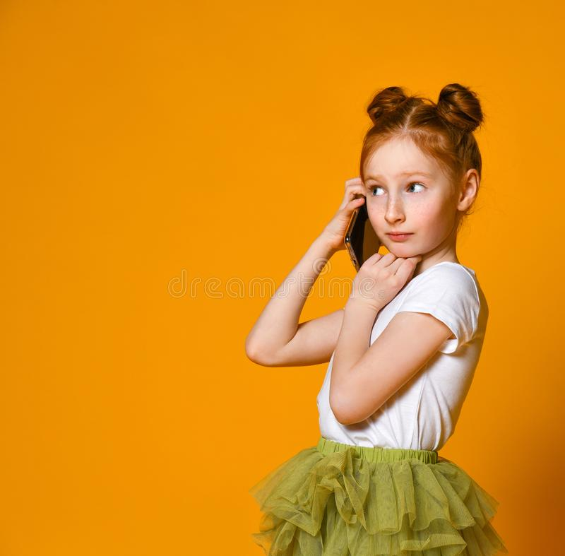 Portrait of the little girl positive that talking on cell phones royalty free stock photography