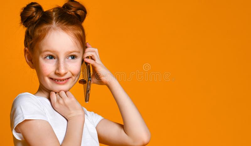 Portrait of the little girl positive that talking on cell phones royalty free stock image