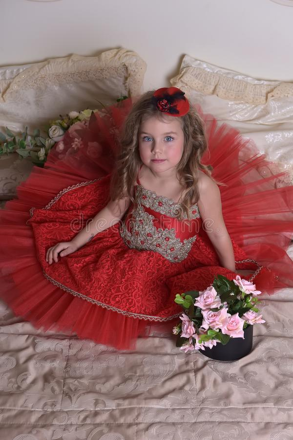 Little girl princess in a red dress and a hat sits on the sofa w royalty free stock photography