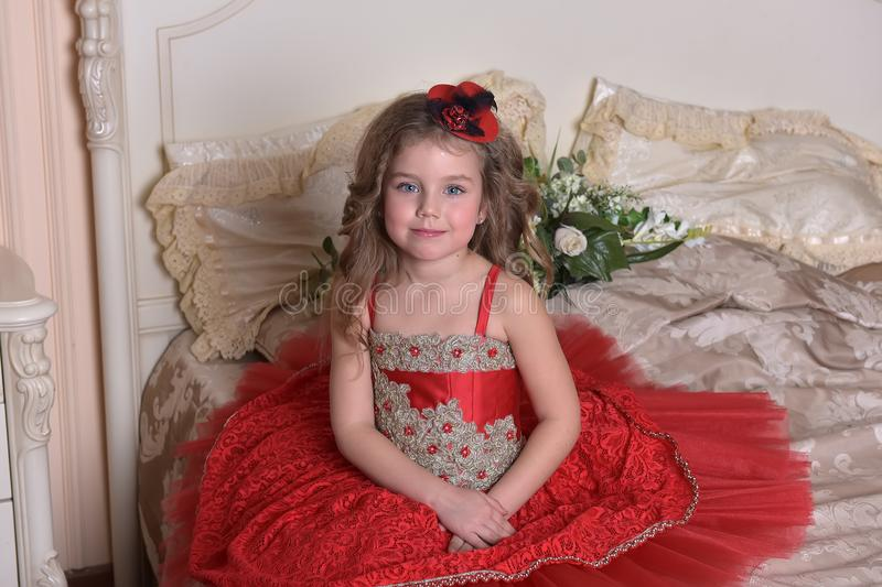 Portrait of a little girl princess in a red dress and hat sitting. On the sofa stock photos