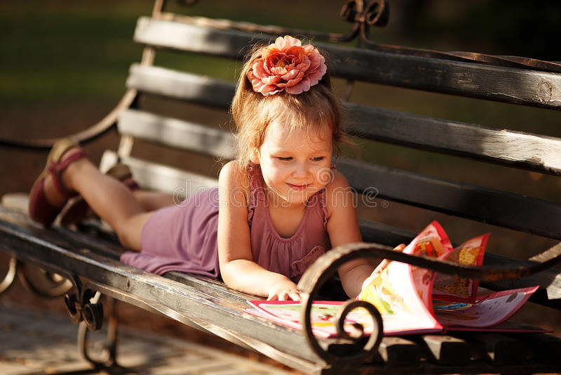 Portrait of a little girl reading a children's book lying on a p. Portrait of a little girl reading a children's book on a park bench stock photo
