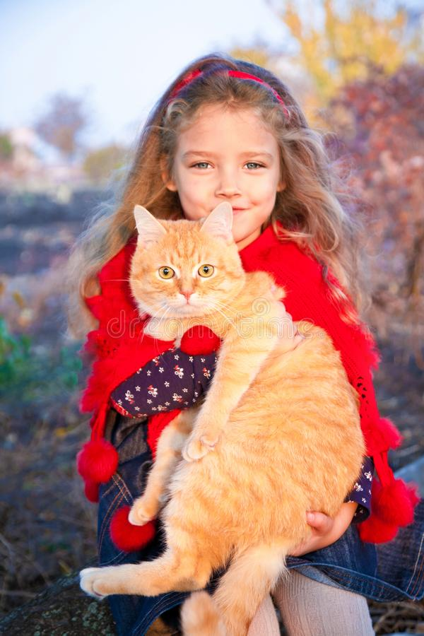 Portrait of a little girl with a red cat in her hands in autumn. Outdoors stock image