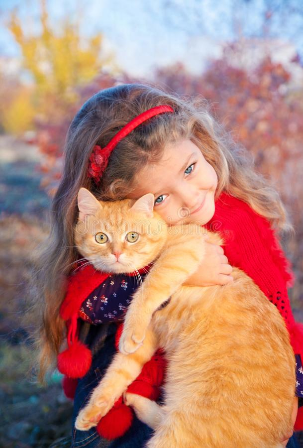 Portrait of a little girl with a red cat in her hands in autumn. Outdoors royalty free stock image