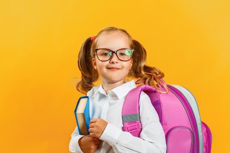 Portrait of little girl schoolgirl with backpack and book on yellow background. Charming child student closeup. Back to school. stock photos